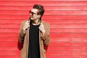 Handsome young man in sunglasses and jacket standing