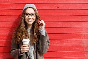 Cheerful cute young woman drinking take away coffee