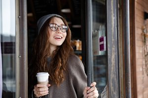 Cheerful lovely young woman drinking take away coffee