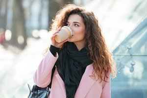 Cute young woman drinking take away coffee.