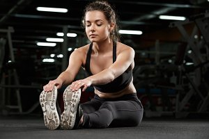 Strong fitness lady make sport stretching exercise in gym.
