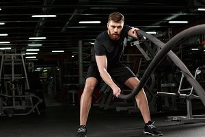 Young strong sports man make sport exercises in gym
