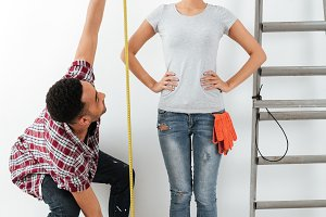 Man and woman using measure tape