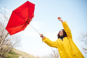 Woman catching flying umbrella
