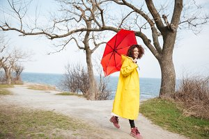 Happy african curly young lady wearing yellow coat holding umbrella