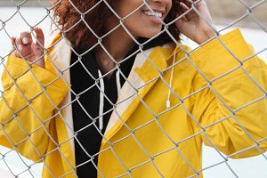 Happy african curly young lady standing near fence outdoors