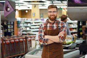 Cashier man on workspace in supermarket shop