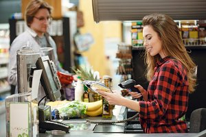 Happy cashier woman on workspace in supermarket shop