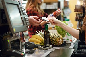 Cropped picture of young man gives credit card to cashier