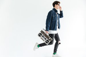 Attractive young man holding boombox. Looking aside.