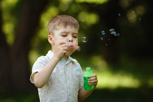 boy inflates bubbles in summer park