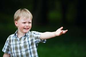 young crying boy in summer park