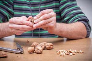 Man opening some walnuts on a table