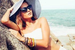 Summer trendy woman posing on ocean seashore