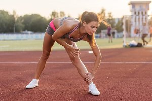 Side view of athletic woman working out on mat in stadium, bending and stretching her back leg muscles