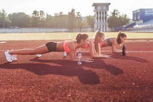Slim athletic women doing planking exercise in the stadium.