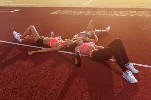 Group of tired fit girls lying on stadiun in circle outdoors