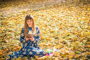 girl reading book in park