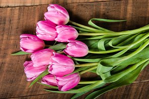 Bouquet of pink tulips on a wooden table