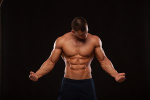 Strong Athletic Man Fitness Model Torso showing six pack abs. isolated on black background with copyspace is looking at himself