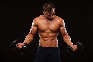 Muscular handsome man is training with dumbbells in gym. isolated on black background with copyspace