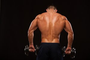 Muscular male model bodybuilder doing exercises with dumbbells, turned back. Isolated on black background with copyspace