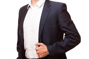 Young handsome businessman in black suit is standing straight and putting his hands in pockets, portrait isolated on white background