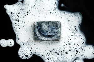 Bar of soap in foam on dark