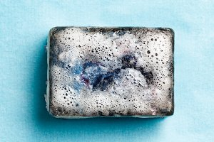Bar of soap in foam on blue