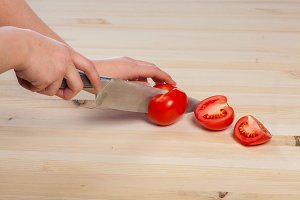 Cutting tomatoes for dishes on the table. Vegetables during the cooking process dishes. Vegetables for healthy eating and dieting