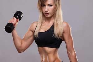 Beautiful athletic woman pumping muscles with dumbbells, isolated on grey background with copyspace