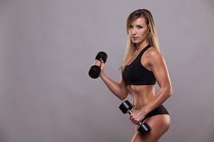 Beautiful fitness woman lifting dumbbells . Sporty girl showing her well trained body . isolated on grey background with copyspace