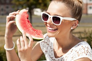 woman smiling and eating watermelon
