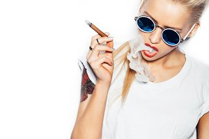 Sexy blonde woman in sunglasses smoking cigar