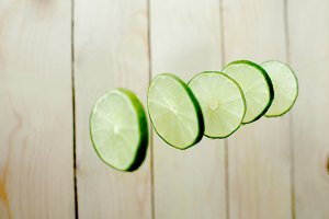 Lime wedges on wooden background