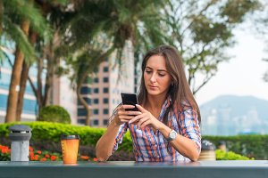 Young woman sitting at a table outdoors using her mobile phone. Female reading text messages on smartphone in the park.