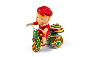 Antique doll: a child on a tricycle