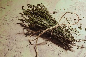 bundle of thyme sprigs on a textural background