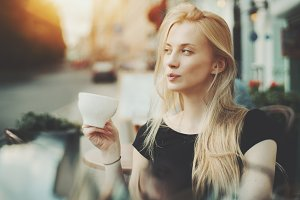 Blonde woman is tasting coffee