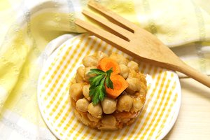 chickpea stew with tomato on plate with wooden cutlery