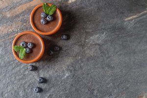 Chocolate mousse with berries in a ceramic bowl. Grey dark background.
