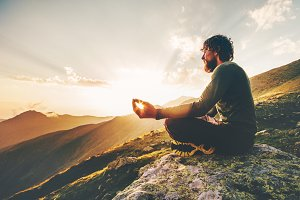 Man meditating at sunset mountains