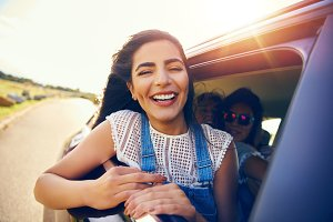Fun loving young woman leaning out of car