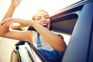 Woman seated in car waves her arms and laughs