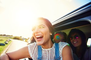Happy excited young woman leaning out of a car