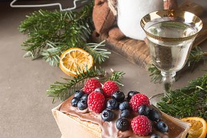 Christmas cake with chocolate frosting, blueberries and raspberries. Dark background.
