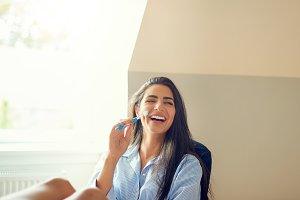 Laughing woman holding toothbrush at home