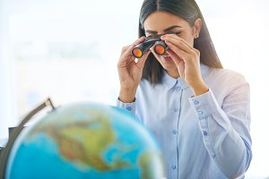 Woman with binoculars looking at globe