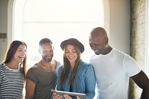 Cheerful group of people looking at tablet