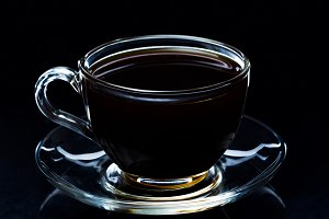 Hot black coffee in a transparent glass cup on a black background